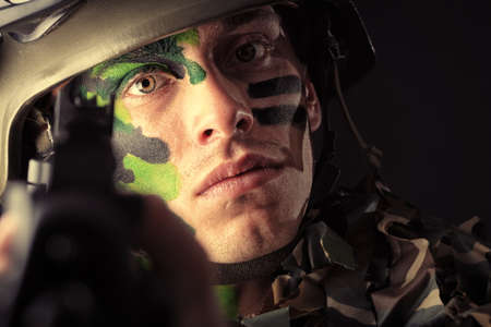 Shot of a conceptual soldier painted in khaki colors. Studio shot over black background. photo