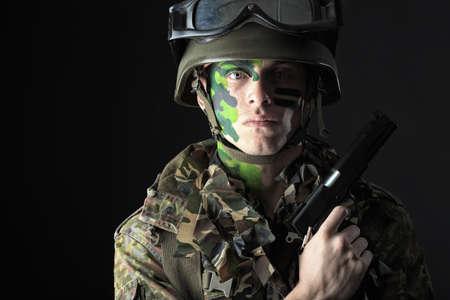 soldado: Captura de un soldado conceptual pintadas en colores caqui. Studio dispar� sobre fondo negro. Foto de archivo