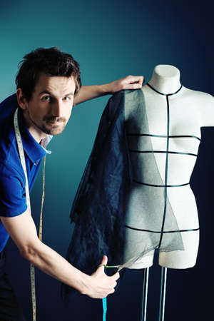 Portrait of a man fashion designer working with dummy at studio. photo
