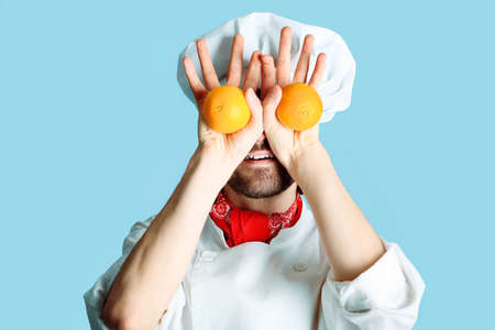 toque: Portrait of a man cook holding oranges. Shot in a studio over grey background.
