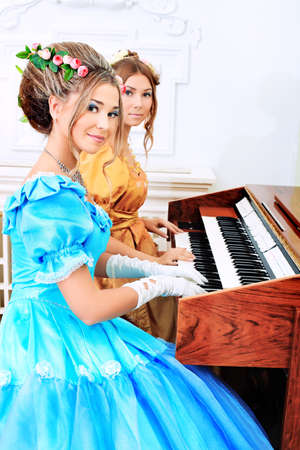 Two beautiful women in medieval era dresses playing the piano. photo