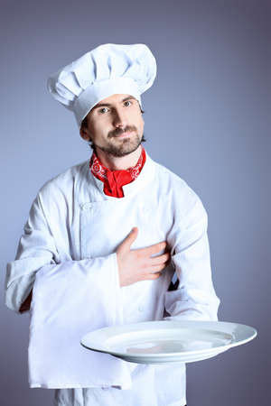toque blanche: Portrait of a man cook holding a plate. Shot in a studio over grey background. Stock Photo