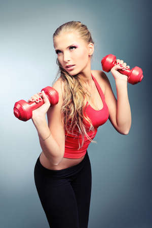 Shot of a sporty young woman with dumbbells. Active sporty life, wellness. photo