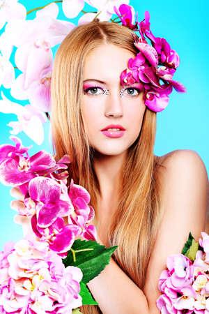 Portrait of a beautiful tanned woman in bikini posing with flowers.