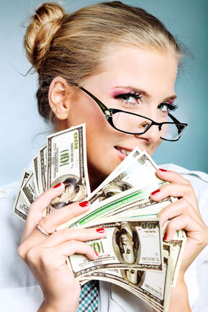 spendings: Beautiful businesswoman holding money. Studio shot over grey background. Stock Photo