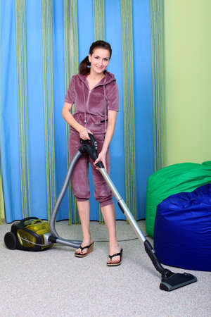 carpet clean: Woman housewife with a vacuum cleaner at home.