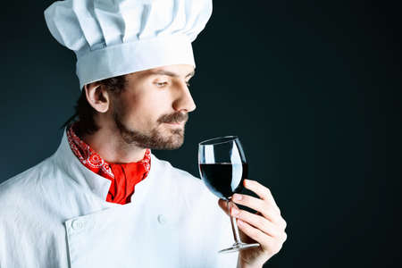 Portrait of a man cook holding a glass of red wine. Shot in a studio over black background. Stock Photo - 9184132