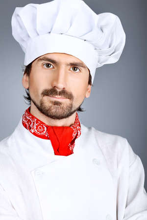 toque blanche: Portrait of a man cook. Shot in a studio over grey background.