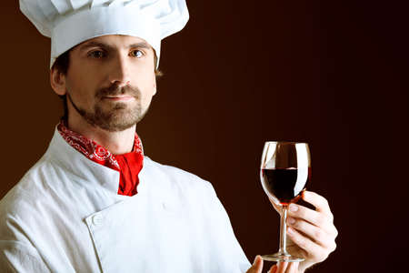 Portrait of a man cook holding a glass of red wine. Shot in a studio over black background. photo