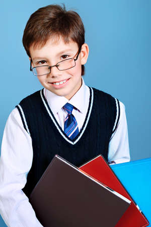 Educational theme: portrait of a schoolboy with books. Studio shot over grey background. photo