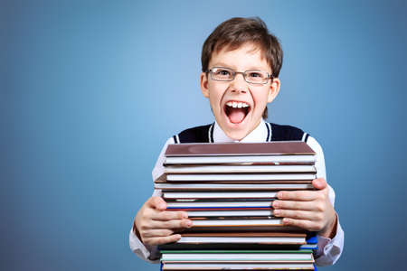 Educational theme: portrait of a schoolboy with books. Over grey background. photo