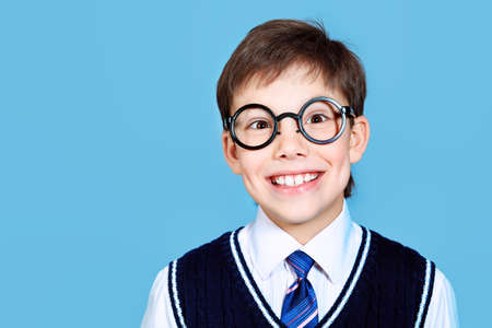Educational theme: portrait of a schoolboy. Studio shot over grey background. photo