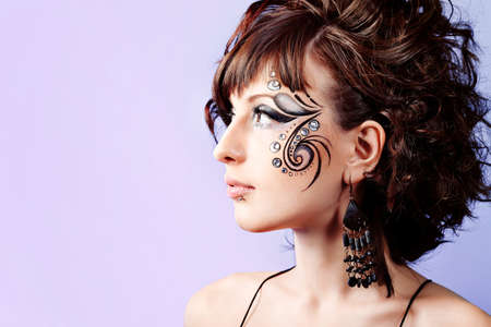 Portrait of beautiful fashionable woman with painted ornament on her face. Studio shot. Stock Photo - 9187158