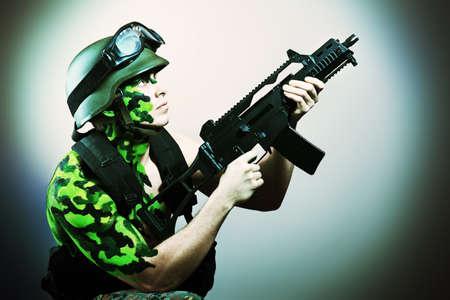 Shot of a conceptual soldier painted in khaki colors. Studio shot.