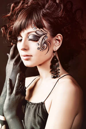 'face painting': Portrait of beautiful fashionable woman with painted ornament on her face. Studio shot. Stock Photo