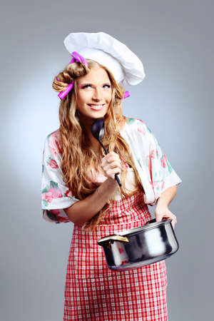 Beautiful blonde woman housewife holding pan. Studio shot over grey background. Stock Photo - 9185643