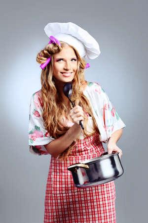 Beautiful blonde woman housewife holding pan. Studio shot over grey background. Stock Photo - 9185643