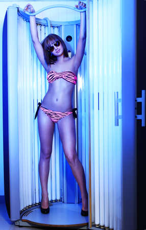 lux: Beautiful young woman tanning in solarium. Beauty, healthcare.