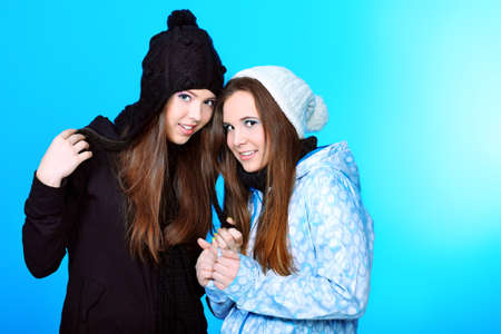 Two happy girls friends. Over blue background. photo