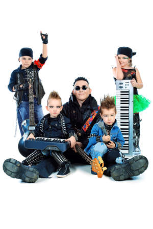 instrumentalist: Heavy metal musician  with a group of stylish children. Shot in a studio. Isolated over white background. Stock Photo