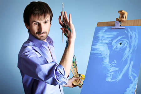artist's model: Portrait of an artist painting on easel. Shot in a studio.