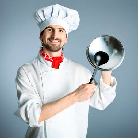 toque blanche: Portrait of a man cook holding a saucepan and ladle. Shot in a studio over grey background.