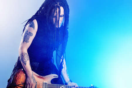 instrumentalist: Heavy metal musician  is playing electrical guitar. Shot in a studio.