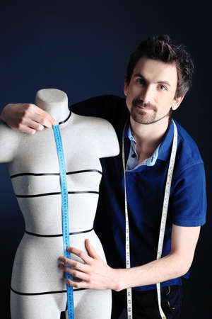 Portrait of a man fashion designer working with dummy at studio. Stock Photo - 9263408