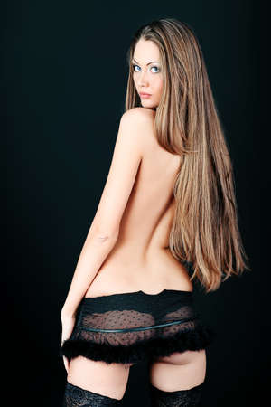Shot of an attractive topless woman in sexual lingerie, over black background.  Stock Photo - 9296960
