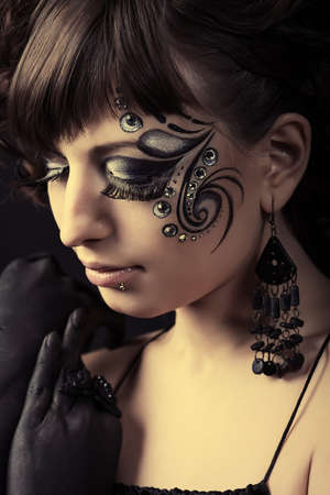 Portrait of beautiful fashionable woman with painted ornament on her face. Studio shot. photo