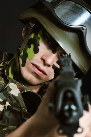 face guard: Shot of a conceptual soldier painted in khaki colors. Studio shot over black background. Stock Photo