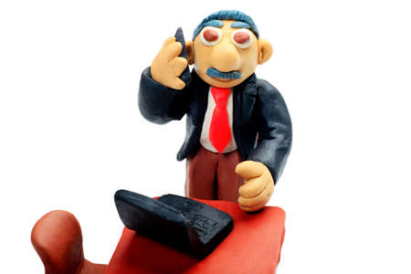 Shot of a plasticine businessman working at the office. Isolated over white background. photo