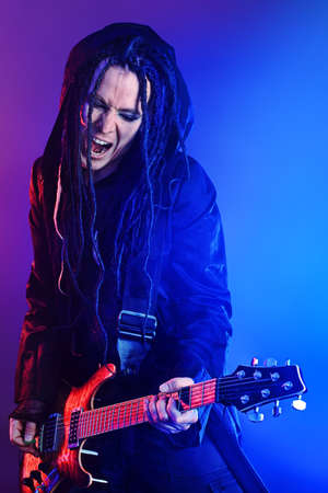 Heavy metal musician  is playing electrical guitar. Shot in a studio. Stock Photo - 9322103