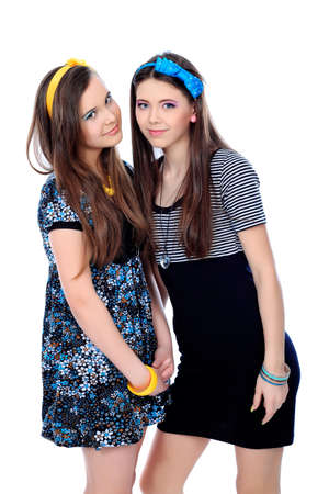 teenage girl dress: Two happy girls friends. Isolated over white background. Stock Photo