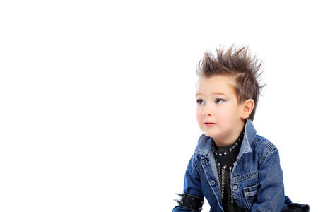 Shot of an emotional little boy wearing rock music clothes. Isolated over white background. photo