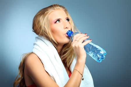 Shot of a sporty young woman drinking water after training. Active lifestyle, wellness. Stock Photo - 9402305