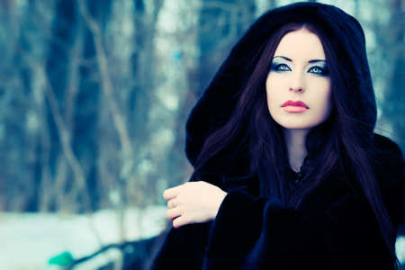 fur tree: Shot of a gothic woman in a winter park. Fashion. Stock Photo