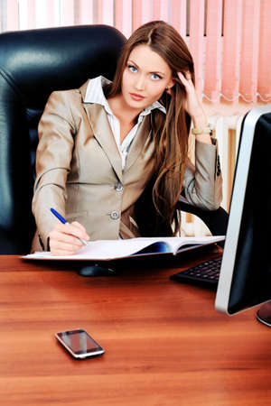 stern: Beautiful business woman is working at the office. Stock Photo