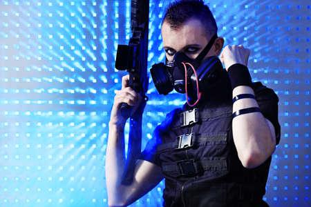 Shot of a conceptual man in a respirator holding a gun. Stock Photo - 9454408