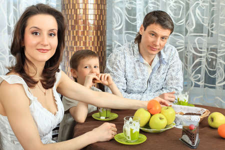 Happy family with a child having a dinner at home. photo