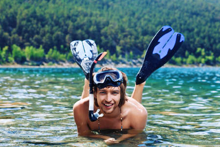snorkelling: Happy young man with snorkelling gear sitting in a sea. Stock Photo
