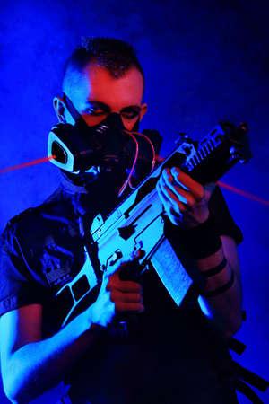 Shot of a conceptual man in a respirator holding a gun.  Stock Photo - 9490158