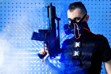 Shot of a conceptual man in a respirator holding a gun.  Stock Photo - 9490154
