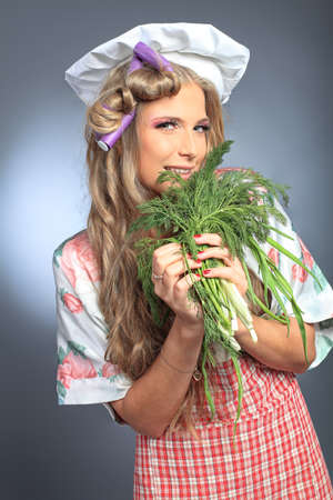 Beautiful blonde woman housewife holding greens and fruits. Studio shot over grey background. photo