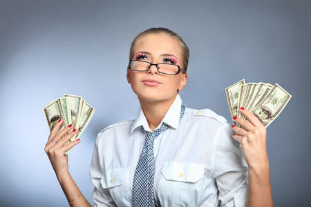 Beautiful businesswoman holding money. Studio shot over grey background. photo