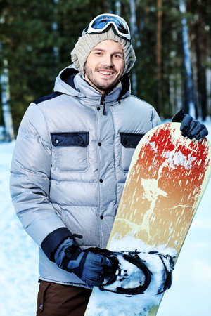 Shot of a young man with a snowboard outdoor. photo