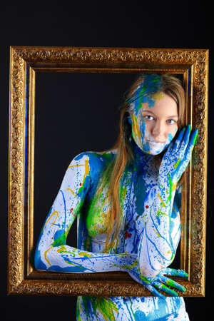 artist's model: Art project: beautiful woman painted with many vivid colors. Over black background.