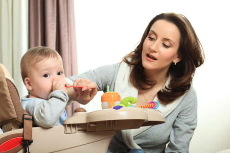 baby feeding: A mother is feeding her baby in the highchair at home.