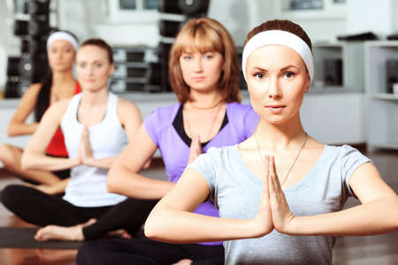 four classes: Group of young women in the gym centre. Yoga.