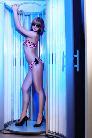 Beautiful young woman tanning in solarium. Beauty, healthcare. photo